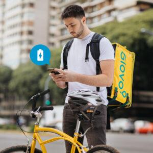 Rider di Glovo di fianco alla propria bicicletta che controlla il cellulare
